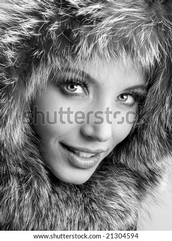Smiling young woman with a fur hood - stock photo
