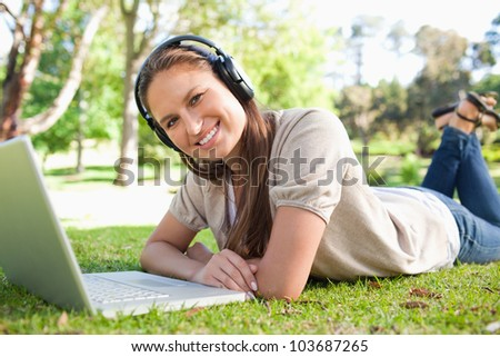 Smiling young woman with a headset and a laptop lying on the lawn