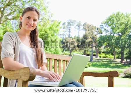 Smiling young woman with a laptop on a park bench