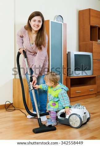 Smiling young woman with a toddler doing house cleaning with a vacuum cleaner - stock photo
