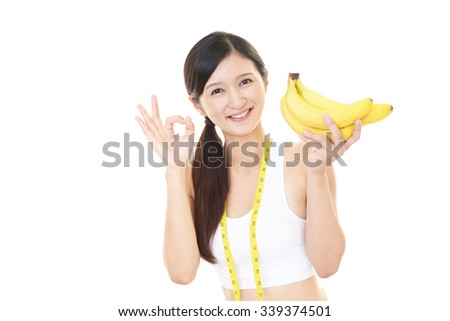 Smiling young woman with banana - stock photo