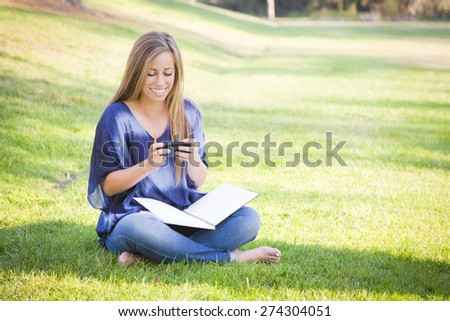 Smiling Young Woman with Book and Cell Phone Outdoors at the Park. - stock photo