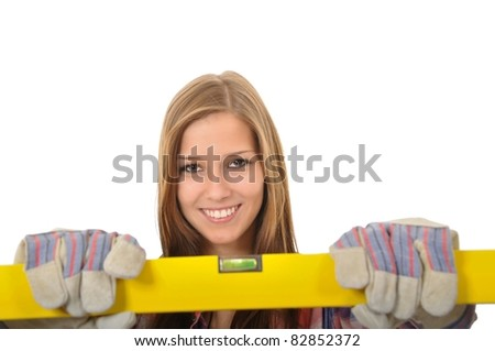 Smiling young woman with brown eyes holding a spirit level - stock photo