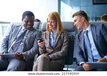 Smiling young woman with cellphone sitting in airport with two male colleagues near by - stock photo