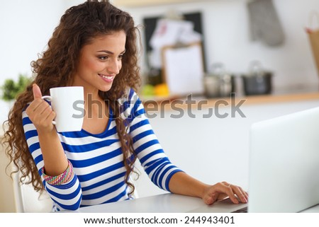 Smiling young woman with coffee cup and laptop in the kitchen at home - stock photo