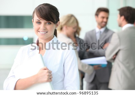 Smiling young woman with colleagues in the background - stock photo