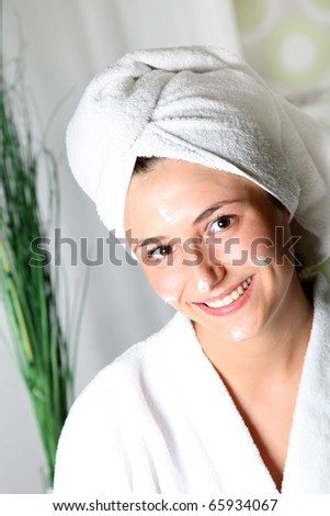 Smiling young woman with cream on her face relaxed. She wears a towel on his head and a bathrobe