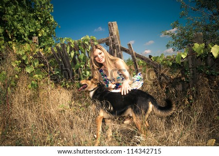 smiling young woman with cute dog at countryside autumn sunny day - stock photo