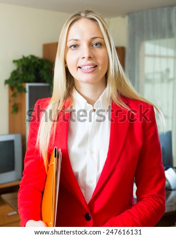 Smiling young woman with documents working in office room - stock photo