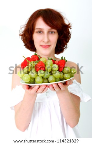 Smiling young woman with grapes, apples and strawberries on a dish - stock photo