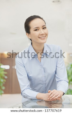 Smiling young woman with hands clasped, portrait