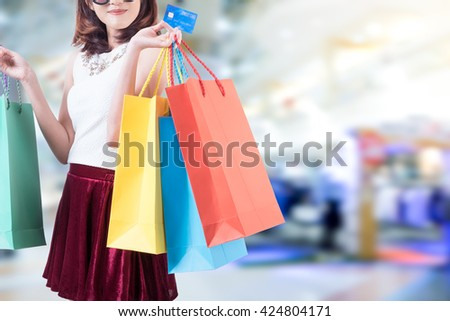 smiling young woman with happiness, credit card ,sale and people concept and shopping bags over mall background - stock photo
