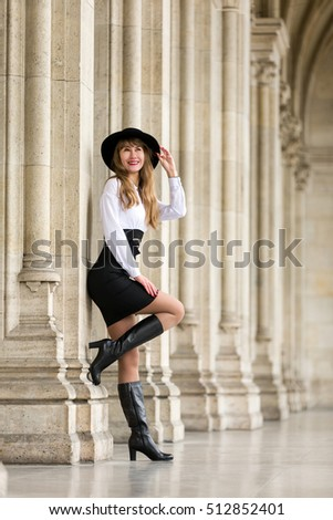 Smiling young woman with hat, boots and dress