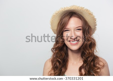 Smiling young woman with hat looking at camera isolated on a white background