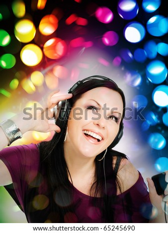 smiling young woman with headphones listening music by mp3 - stock photo