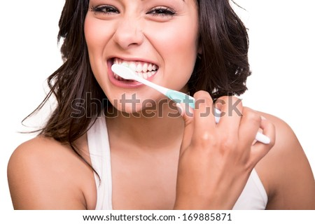 Smiling young woman with healthy teeth holding a tooth brush - stock photo