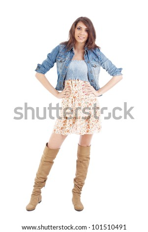 Smiling young woman with her arms akimbo - stock photo