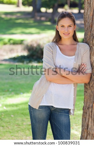 Smiling young woman with her arms crossed leaning against a tree - stock photo