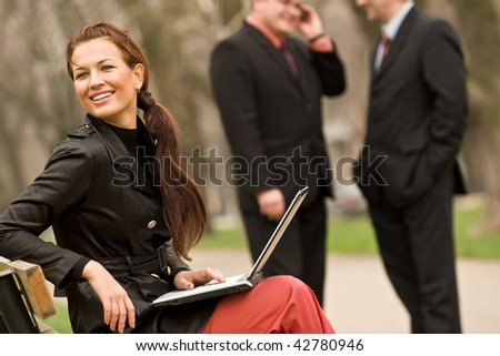 Smiling young woman with laptop and colleagues
