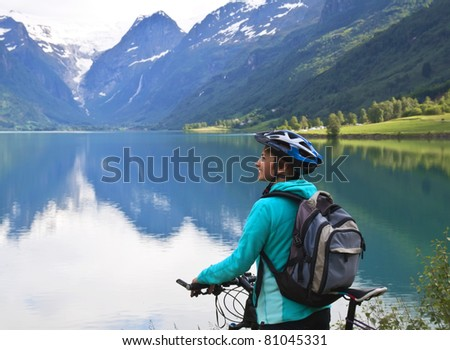 Smiling young  woman with mountain bike - stock photo