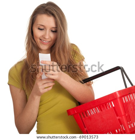 smiling young woman with red basket checking purchases list - stock photo