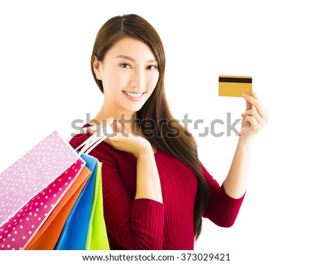 smiling young woman with shopping bags and credit card - stock photo