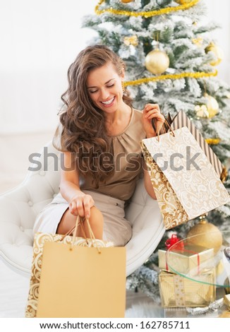 Smiling young woman with shopping bags near christmas tree - stock photo