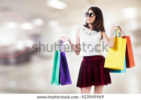 Smiling young woman with shopping bags over mall background with copy space. - stock photo