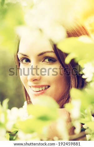 Smiling young woman with spring blossom flowers. Filtered image  - stock photo