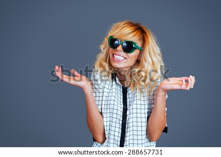 Smiling young woman with sunglasses making a gesture