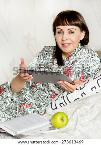 Smiling young woman with tablet on her bed room - stock photo
