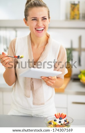 Smiling young woman with tablet pc eating fruit salad - stock photo