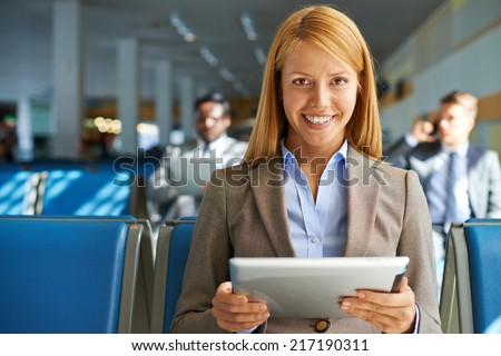 Smiling young woman with touchpad sitting in airport with two colleagues on background - stock photo