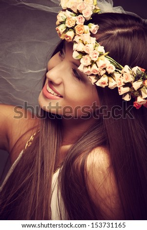 smiling young woman with wreath of flowers and veil in hair studio shot - stock photo