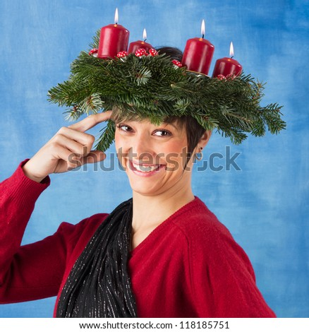 Smiling young woman woman wearing advent wreath on the head taps her forehead. Funny studio shot against a blue background, series - stock photo