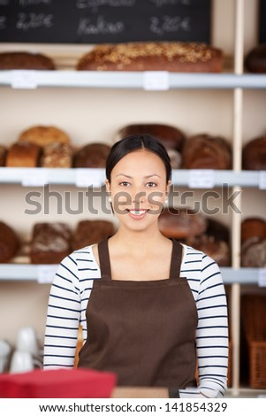 smiling young woman working at coffeeshop counter