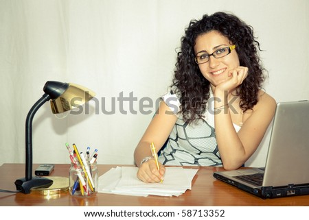 smiling young woman working at her desk in office - stock photo