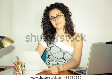 smiling young woman working at her desk in office