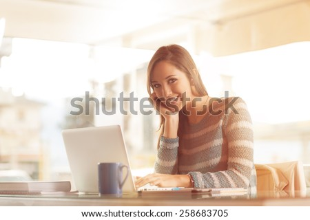 Smiling young woman working at office desk with her laptop - stock photo