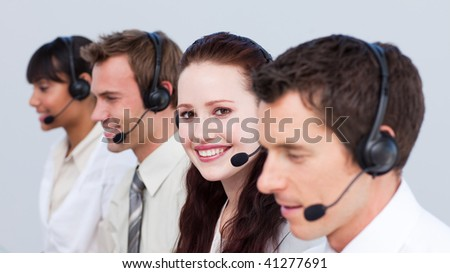 Smiling young woman working in a call center with her colleagues - stock photo