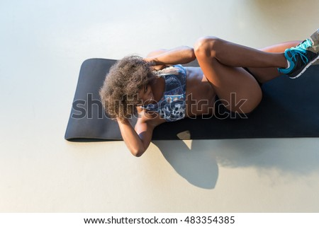 smiling young woman working out at fitness center doing crunch abdominal sit-ups