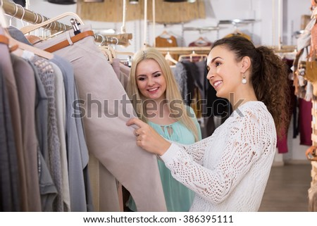 Smiling young women buying pants at the apparel store