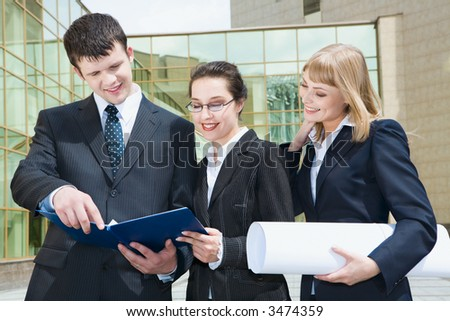 Smiling young women showing documents to their boss and a businessman attentively reading them outside the building with glassy walls