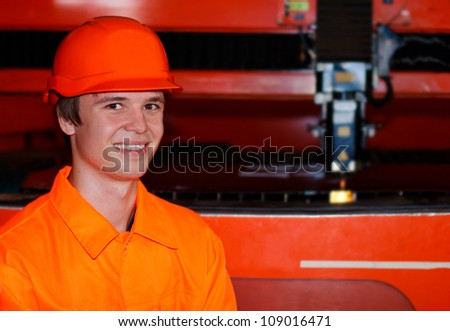 Smiling young worker near a laser