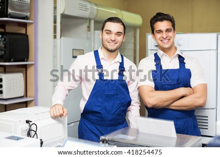 Smiling young workers in uniform working at household appliances store - stock photo