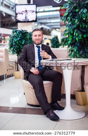Smiling ypung businessman drinking coffee - stock photo