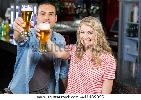 Smilinh couple holding beer in a bar - stock photo
