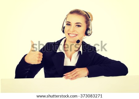 Smille call center woman holding empty banner and showing OK - stock photo