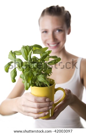 Smilled girl  is passing basil. Selective focus. - stock photo