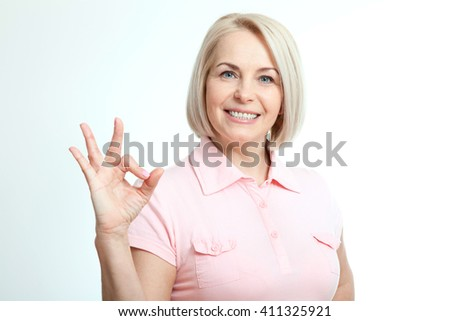 Smilling attractive middle aged woman showing thumbs up, okay. Isolated